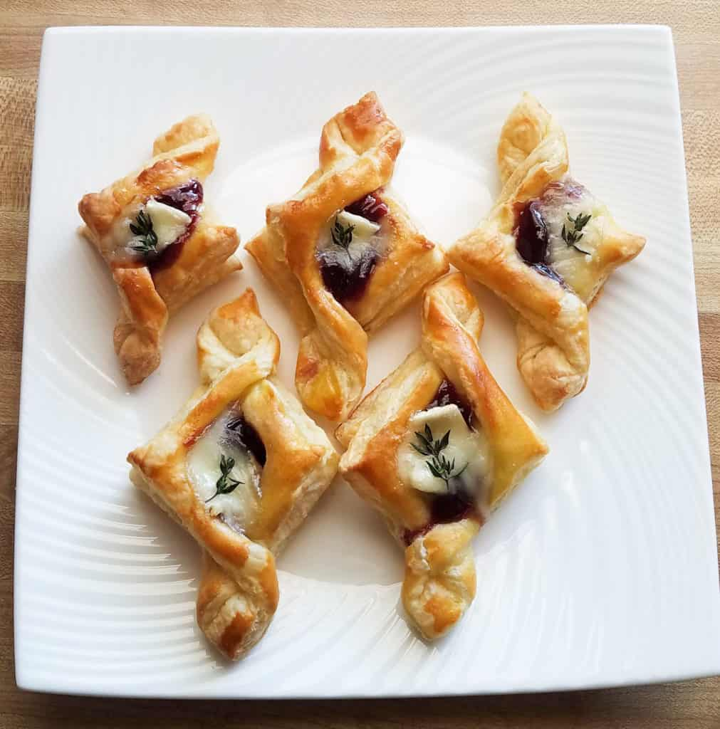 A plate of raspberry brie tartlets. Serve this delicious puff pastry recipe at your next Christmas party!