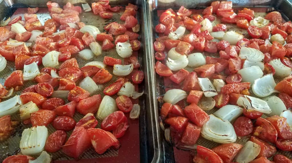 Two sheet trays of roasted tomatoes, onions, and garlic.