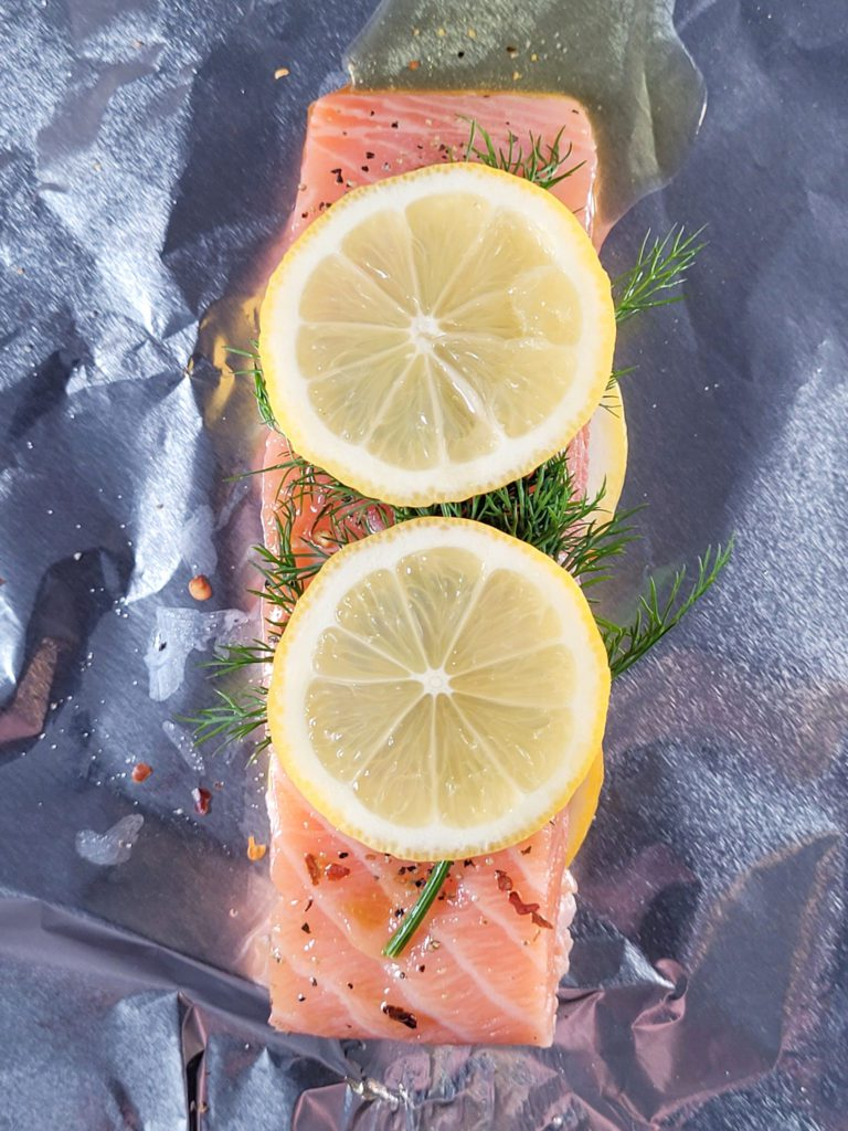 Raw salmon with lemon and dill on tinfoil.