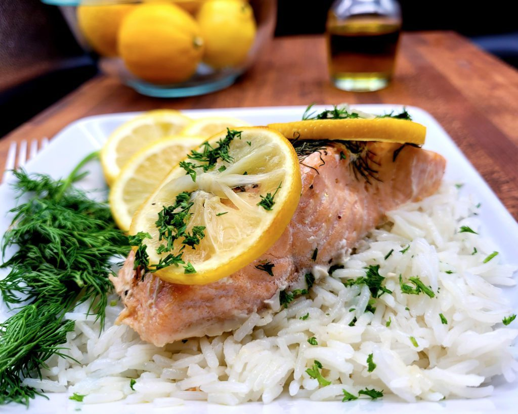 Easy and healthy oven baked salmon with lemon and dill on a square plate.