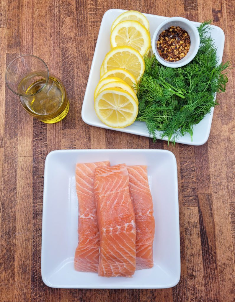 The ingredients to make oven baked salmon: salmon, lemon, dill, olive oil, and red pepper flakes.