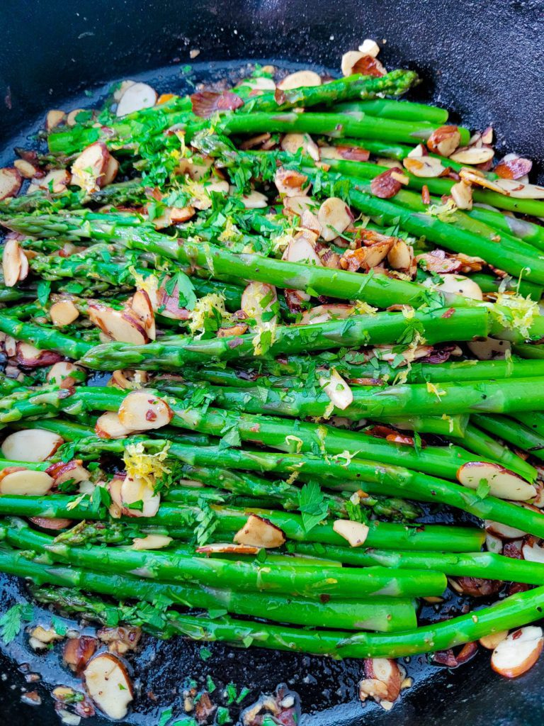 A close up of asparagus amandine in a cast iron skillet.